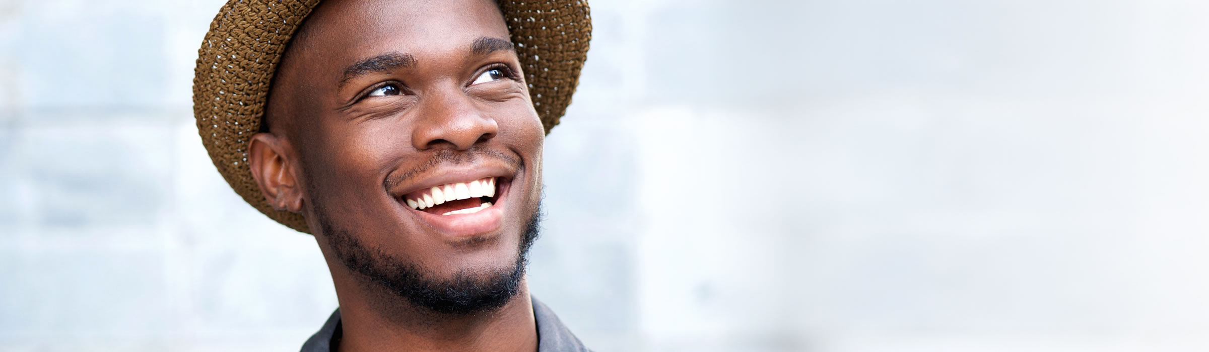 Young man wearing hat smiling. Dental implant gallery for our Watford dentist, Senova Dental Studios in Hertfordshire