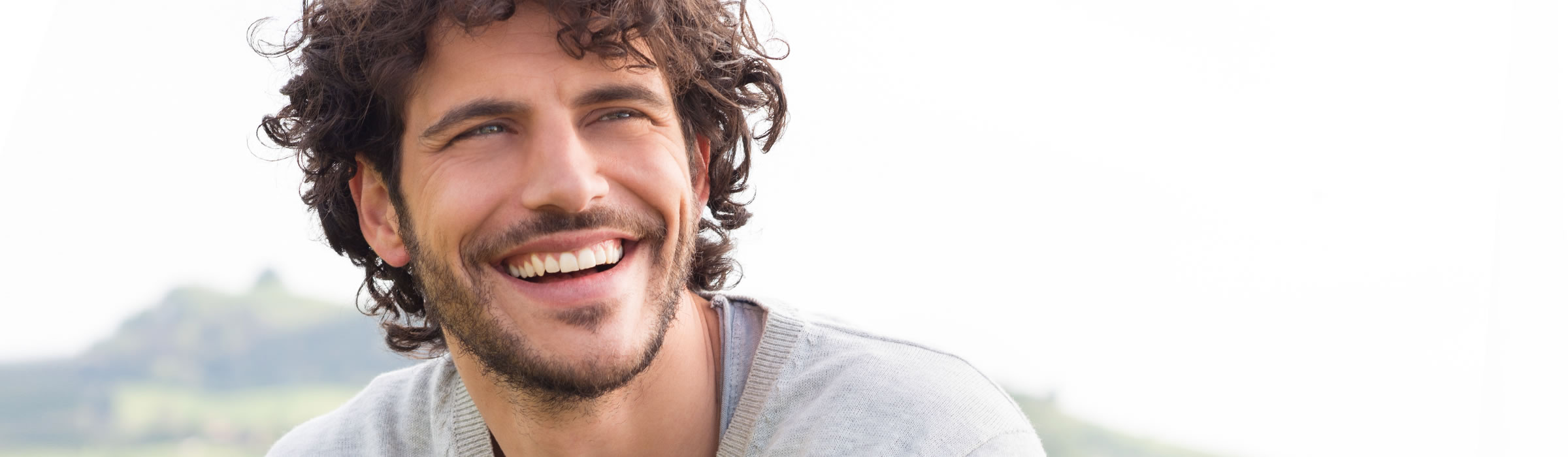 Man laughing. Cosmetic dentist Watford offering inlays and onlays. Senova Dental Studios in Watford, Hertfordshire